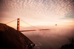 Sunset over the Golden Gate Bridge. This picture shows the cloud speckled sky with the sun setting in the distance above the Golden Gate Bridge in San Francisco stock images