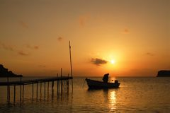 Sunset over a Greek island.. A lone individual in a boat cast against a brilliant orange sunset.  Horizontal orientation Stock Photos