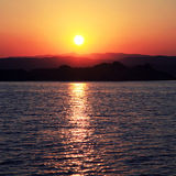 Sunset over a greek island in the Mediterranean sea Stock Photos