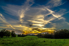 Sunset over green field farm land Royalty Free Stock Image