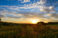 Sunset over green fields Royalty Free Stock Photos
