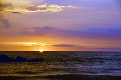 Sunset over the Gulf of Mexico. A sunset with rocks in the foreground and birds in flight Stock Photos