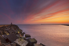 Sunset over harbour entrance at sea in The Netherlands Stock Image