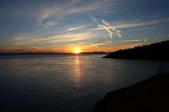 Sunset over Haro Strait. Sunset taken from San Juan Island looking over Haro Strait with contrails in the darkening sky. Includes a reflection of the sun and Stock Photo