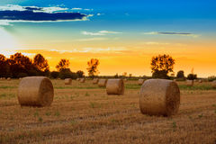 Sunset over the hay bale field Stock Photos