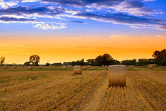 Sunset over the hay bale field Royalty Free Stock Photography