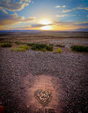 Sunset over a heart made of pebbles stock photography