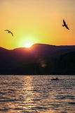 Sunset over the hill. Sunset behind the mountain, the Golden sky, the shadows of birds Royalty Free Stock Photo