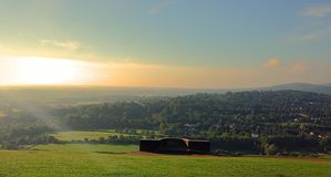 Sunset over a hill top view. Blue sky and sun setting over a hill Stock Photo