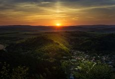 Sunset over the hills and a village. Sunset over the hills with a little village in valley Stock Photos