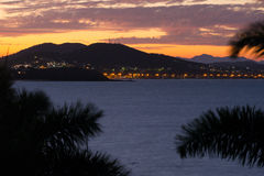 Sunset over hills and water. Palm trees frame the lights of Yeppoon under a vivid sunset on Queensland`s Capricorn Coast, Australia Stock Images