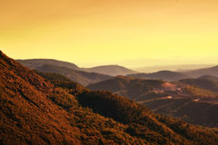 Sunset over hilly terrain in southern France. Beautiful orange and yellow colored image of mountains and sky at sunset Stock Image