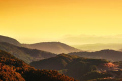 Sunset over hilly terrain in southern France. Beautiful orange and yellow colored image of mountains and sky at sunset Stock Images