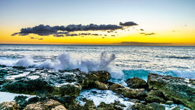 Sunset over the horizon with a few clouds and the rocky shores of the west coast of Oahu Royalty Free Stock Images
