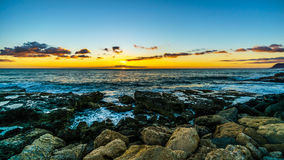 Sunset over the horizon with a few clouds and the rocky shores of the west coast of Oahu. Sunset over the horizon with a few clouds and the rocky shores of the Royalty Free Stock Photography