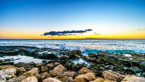 Sunset over the horizon with a few clouds and the rocky shores of the west coast of Oahu Stock Photo