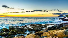 Sunset over the horizon with a few clouds and the rocky shores of the west coast of Oahu Stock Images