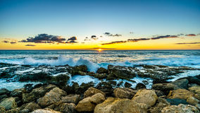 Sunset over the horizon with a few clouds and the rocky shores of the west coast of Oahu Stock Photography