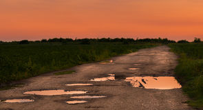 Sunset over the horizon. Ground road in the field at sunset, beautiful orange sky Stock Photography
