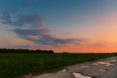 Sunset over the horizon. Ground road in the field at sunset, beautiful orange sky Stock Images