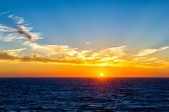 Sunset over horizon at sea Stock Image
