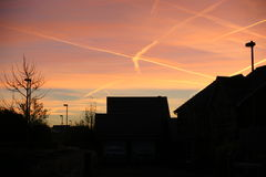 Sunset over houses with aircraft contrails Royalty Free Stock Photos