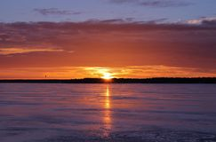 Sunset over the ice on Stadsfjärden in Luleå. The sun sets over Bergnäset and reflected in the shiny ice Royalty Free Stock Images