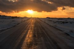 Sunset over an icy road in Iceland. This photo shows a warm winter sunset over a road in Iceland stock photography