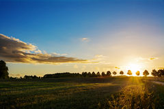 Sunset over a idyllic country landscape with fields and trees Stock Image
