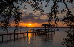 Sunset over Indian River, Florida. Orange and yellow sunset over Indian River, Melbourne, Florida with narrow wooden  jetty poking out into the river and framed Royalty Free Stock Photos
