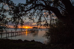 Sunset over Indian River, Melbourne Beach, Florida. Sunset over wooden pier in Indian River, Melbourne Beach, Florida, USA Stock Photo