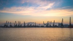 Sunset over industrial cranes and cargo ships in port Varna, Bulgaria. Colorful sunset over sea port and industrial cranes, Varna, Bulgaria. Panoramic view stock video footage