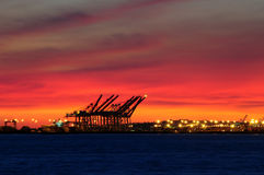 Sunset over industrial port. Beautiful sunset over cranes by side of docks in industrial port Stock Photos