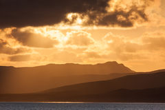 Sunset over Islay from the Islay ferry. Dramatic ridgelines receeding into the distance captured in the dramatic November sunset over Islay, Scotland, UK Royalty Free Stock Photos