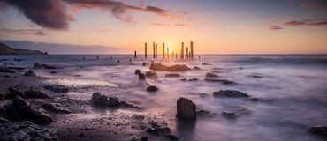 Sunset over jetty remains Royalty Free Stock Photo