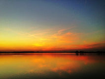 Sunset over lake. Fiery sunset over lake surface Royalty Free Stock Images