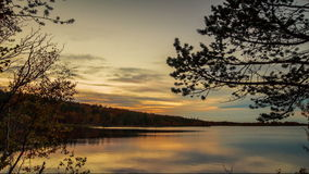 Sunset over lake in Autumn time lapse. Sunset over the lake in the fall with the trees framing the image in the foreground stock video footage