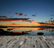 Sunset over a lake and blue bricks floor Royalty Free Stock Photography