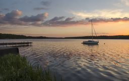 Sunset over lake. Boat in lake and beautiful clouds royalty free stock photo
