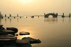 Sunset over lake and bridge. Sunset view over West Lake, China with people walking across a bridge Stock Photography