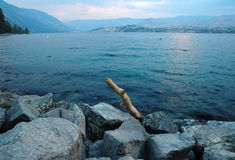 Sunset over the Lake Chelan. With rocks and driftwood in foreground Royalty Free Stock Image