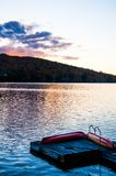 Sunset over lake with dock and canoes during Indian Summer in Quebec, Canada. Sunset over lake with dock and red canoes during Indian Summer in Quebec, Canada Stock Image