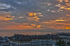Sunset over lake Geneva with Lausanne in foreground. Dramatic sunset on a summer evening with cloudy sky - taken from Lausanne, Switzerland Royalty Free Stock Photography