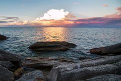 Sunset over Lake Malawi. Sunset through clouds over Lake Malawi with rocks in foreground royalty free stock image