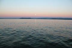 Sunset over Lake Neuchatel, Switzerland. Moon rising over Lake Neuchatel, Switzerland Stock Image