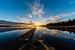 Sunset over a lake in Nykroppa, Filipstad, Sweden with a jetty. In front Royalty Free Stock Photography