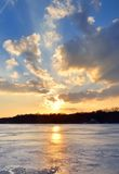 Sunset over the lake. The setting sun shines over frozen lake royalty free stock image