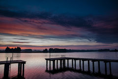 Sunset over the lake. Silhouette bridge by the lake in the evening at twilight Stock Photo
