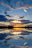 Sunset over the lake on a sky background with planets Stock Photos