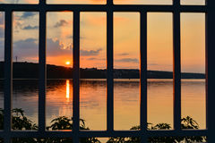 Sunset over a lake, sky. Lattice. Prison. Sunset over a lake with clouds and sky red, blue, orange and blue. Lattice. Prison Stock Photos